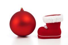 Esfera y bota rojas de la Navidad en el fondo blanco foto de archivo