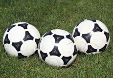 Esferas de futebol na grama Imagens de Stock