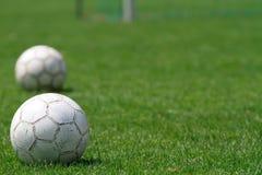 Esferas de futebol no campo de futebol Imagens de Stock