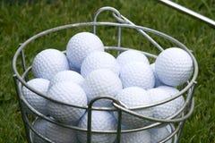 Esferas de golfe na cubeta no verde Imagem de Stock Royalty Free
