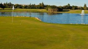 Esferas de golfe no furo Fotografia de Stock Royalty Free