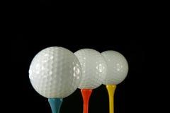 Esferas de golfe no preto imagem de stock
