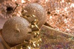 Esferas de vidro douradas no backgroun brilhante do Natal Imagens de Stock