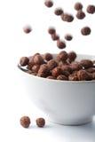 Esferas do chocolate que caem na bacia isolada Fotografia de Stock
