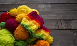 Esferas do fio colorido O processo de fazer malha tampões imagens de stock