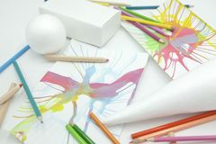 Esferas, prisma e cone brancos com lápis coloridos e pinturas abstratas no fundo branco foto de stock royalty free