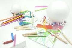 Esferas, prisma e cone brancos com lápis coloridos e pinturas abstratas no fundo branco imagem de stock