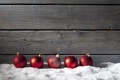 Esferas rojas de la Navidad en la pila de nieve contra la pared de madera fotografía de archivo libre de regalías