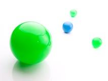 Esferas verdes y azules brillantes en blanco. Imágenes de archivo libres de regalías