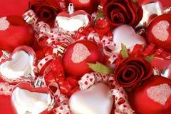 Esferas vermelhas do cetim, corações de prata com rosas e ribb Imagens de Stock