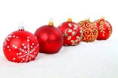 Esferas vermelhas do Natal na neve Fotos de Stock Royalty Free