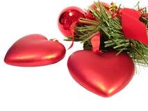 Esferas vermelhas e corações do Natal congratulatório em uma pele-árvore? Br de s Foto de Stock Royalty Free