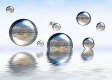 Esferas vidriosas que flotan en el agua Foto de archivo