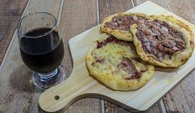 Esfiha árabe delicioso, con los rellenos queso y carne con el tomate y la cebolla Servido en un tablero de madera imágenes de archivo libres de regalías
