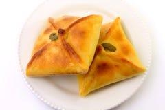 Esfiha цыпленка арабского начала традиционно приспособленное для бразильской кухни на плите на белой предпосылке стоковые фото