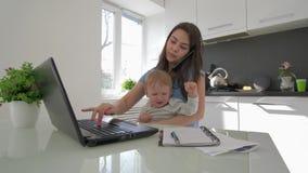 Esforço da família, mum a multitarefas com o menino infantil de grito ao trabalhar no laptop e ao falar no telefone celular filme