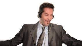 Esforço dos escapes do homem de negócios que escuta a música video estoque