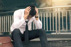 Esforço novo asiático do homem de negócios que senta-se no escritório principal com suas mãos que cobrem sua cabeça contra fotografia de stock royalty free