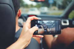Żeńska bierze fotografia z telefon komórkowy kamerą z pojazdem podczas wycieczki samochodowej Zdjęcia Stock