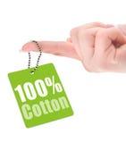Żeńska ręka pokazuje sto procentów bawełnianą etykietkę Zdjęcia Royalty Free