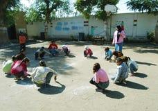 Żeński nauczyciel w kierowniczym szaliku przy szkolnym kolekcjonowaniem dziewczyny w okręgu i rysunku na piasku Fotografia Stock