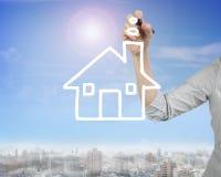 Żeński ręki mienia pióra rysunku domu kształt chmurnieje w niebie Obraz Stock