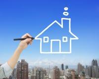Żeński ręki mienia pióra rysunku domu kształt chmurnieje w niebie Fotografia Stock