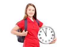 Żeński uczeń trzyma ściennego zegar Zdjęcie Royalty Free