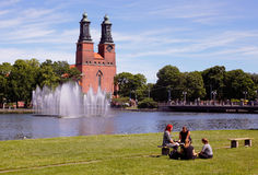 Eskilstuna. Sweden - June 19, 2017: A group of four people sitting in the park at the waterfront in downtown  with the Klosters church in the background Stock Photography