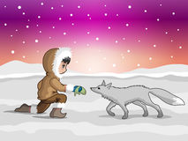 Eskimo boy making friends with polar fox Stock Photo