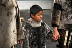 Eskimo child. Holding his mother by her hand stock image