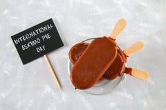 Eskimo paj för glass på en pinne med text på en grå bakgrund Begrepp för för eskimåpaj för ferie den internationella dagen fotografering för bildbyråer