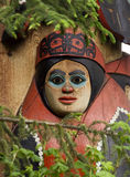 Eskimo totem pole. Closeup of painted head on traditional Eskimo totem pole surrounded by leafy branches, Anchorage, Alaska, U.S.A Stock Photos