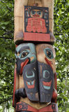 Eskimo totem pole. Painted faces on Eskimo totem pole with leafy green background, Anchorage, Alaska, U.S.A Stock Images