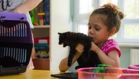 Eskisehir, die Türkei - 5. Mai 2017: Kleines Vorschulmädchen, das ein schwarzes Kätzchen in ihren Händen in einem Klassenzimmer h Lizenzfreie Stockfotografie