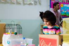 Eskisehir, die Türkei - 5. Mai 2017: Kleines Vorschulmädchen, das einen Vogel in einem Käfig in einem Klassenzimmer betrachtet Lizenzfreie Stockbilder