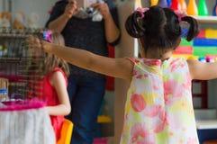Eskisehir, die Türkei - 5. Mai 2017: Kleines Vorschulmädchen mit dem Kleid, das ihre Mutter mit den offenen Armen im Kindergarten Stockbilder