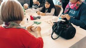 People attending a workshop and exhibition called Arzu'nun Bebekleri in Eskisehir. Eskisehir, Turkey - April 08, 2017: Women creating handmade art dolls in group stock footage