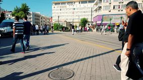 People in the streets on summertime in downtown Eskisehir. Eskisehir, Turkey - July 31, 2017: Crowd of people walking at the center of the city on a sunny day stock footage