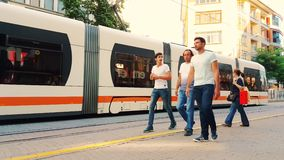 Urban tram passing by the city center in Eskisehir, Turkey. Eskisehir, Turkey - July 31, 2017: Modern tramway leaving the station, people walking in the street stock video