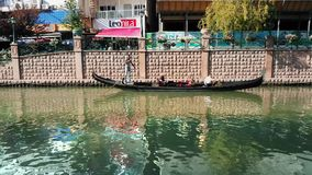 People enjoying the gondola tour in Porsuk River, Eskisehir. Eskisehir, Turkey - July 31, 2017: Romantic tour in gondola, rowed by a gondolier in Porsuk River stock footage