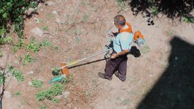 Top view of a worker mowing grasses in the backyard. Eskisehir, Turkey - July 19, 2018: Top view of a man working with lawnmower in the garden stock video footage