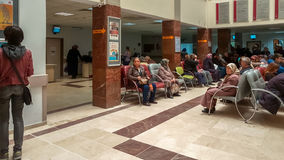 Eskisehir, Turkey - March 28, 2017: People waiting for a doctor. Eskisehir, Turkey - March 28, 2017: Row of multiethnic people sitting side by side while waiting royalty free stock photography