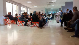 Eskisehir, Turkey - March 28, 2017: People waiting for a doctor. Eskisehir, Turkey - March 28, 2017: Row of multiethnic people sitting side by side while waiting stock photo