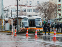 Eskisehir, Turkey - March 13, 2017: People walking in the street. At the center of the city on a rainy day. Tramways waiting at the station Royalty Free Stock Photos
