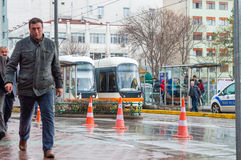 Eskisehir, Turkey - March 13, 2017: People walking in the street. At the center of the city on a rainy day. Tramways waiting at the station Royalty Free Stock Images