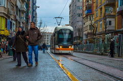 Eskisehir, Turkey - March 13, 2017: People walking in the street. At the center of the city while a tramway passing Stock Photography