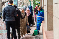 Eskisehir, Turkey - March 13, 2017: People walking in the street. On a rainy day. A municipal worker is leaning on the wall and talking on her mobile phone Royalty Free Stock Photos