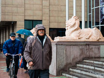 Eskisehir, Turkey - March 13, 2017: People walking in the street. On a rainy day. View of lion sculptures in front of the metropolitan municipality Stock Images