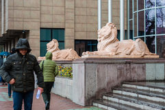 Eskisehir, Turkey - March 13, 2017: People walking in the street. On a rainy day. View of lion sculptures in front of the metropolitan municipality Stock Photo